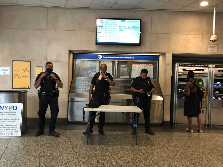Three police officers at a subway bag check at a subway station; one is masked, two are not (one of the two is drinking from a cup)