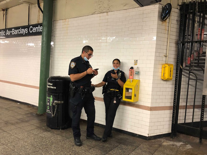 Two NYPD officers at a subway station with their masks pulled down