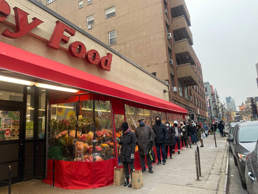 New Yorkers wait in line at a key food supermarket as many residents rushed to get groceries before the snowstorm.