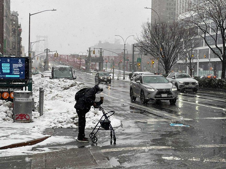 A person using a walker attempts to cross a slushy corner of Delancey Street in Manhattan.