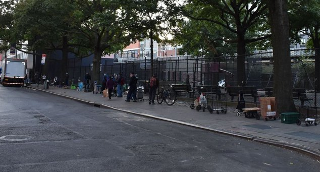 A line of people wait to receive assistance from La Jordana food pantry, with several push carts left unattended.