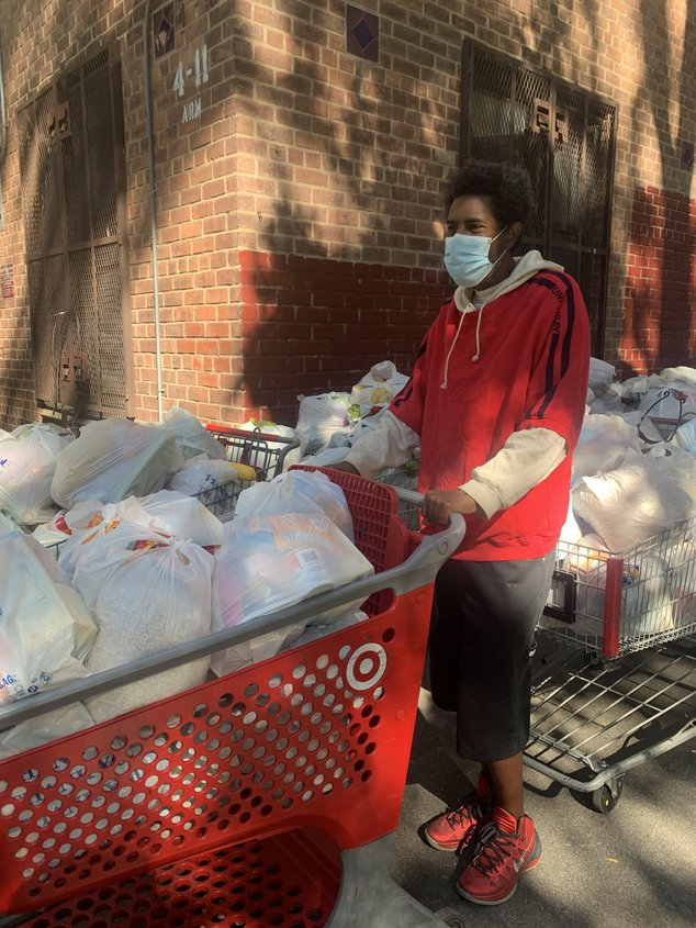 A man wearing a red sweater and a mask over his mouth stands holding onto a cart full of groceries for La Jordana food pantry clients in Flushing.