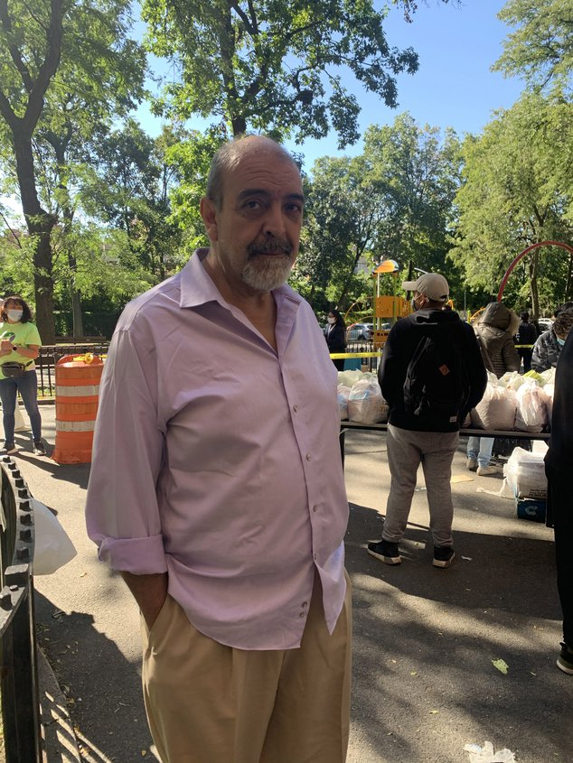 Pedro Rodriguez, a middle-aged man with a beard and no hair wearing a pink button shirt and light yellow pants, stands for a photo outside a staging area for food distribution. Rodriguez is the found and executive director of La Jornada.