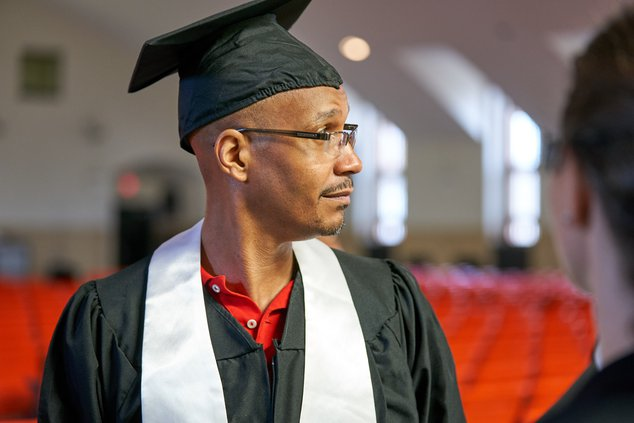 Sheldon Johnson wearing a cap and gown at a graduation ceremony.