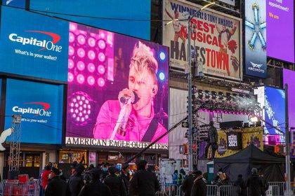 A billboard shows Machine Gun Kelly performing