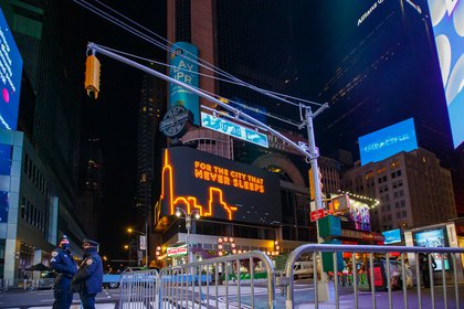 "A billboard in the empty Times Square says ""For the city that never sleeps"""
