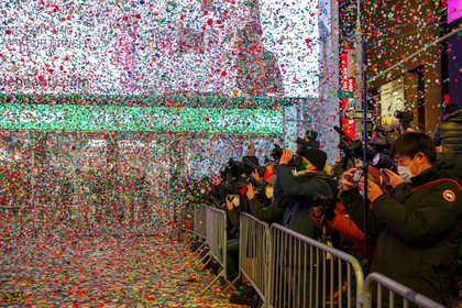 People on the perimeter of the barricades photograph a waterfall of confetti