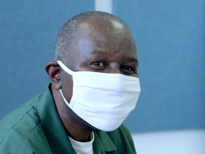A picture of prisoner Yohannes Johnson, 64, wearing a white mask.