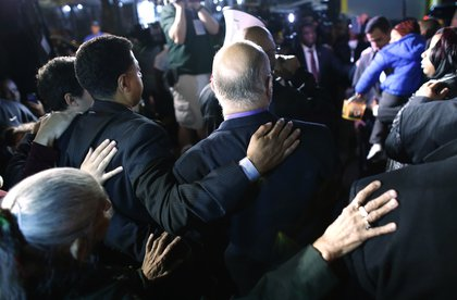 Police officers embrace each other at the vigil<br/>