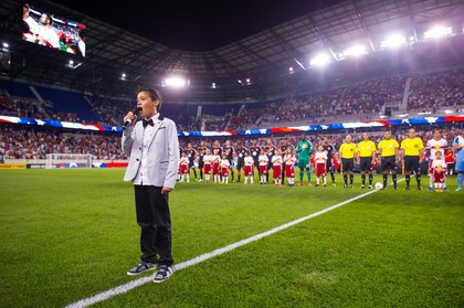 10-year-old Kyah Cahill sings the national anthem as his father looks on. (Rob Tringali/New York Red Bulls)
