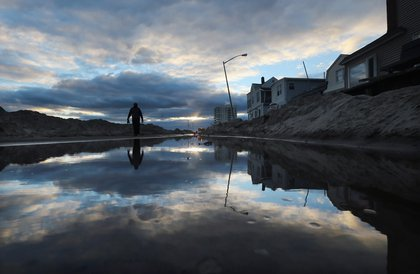 A man walks next to standing water and piles of sand swept onto a road from Superstorm Sandy at Rockaway Beach on November 3, 2012 in Queens. <br/>
