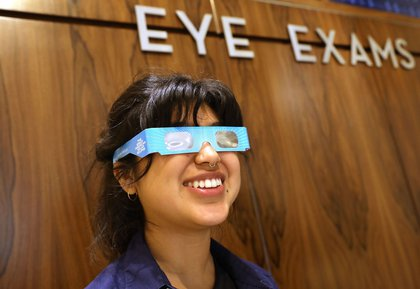 An employee at Warby Parker tries on viewing glasses in NYC<br>
