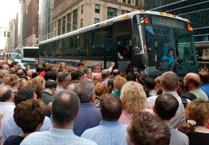Commuters crowd around a bus in Midtown on August 14, 2003 (LOUIS LANZANO/AP/Shutterstock)