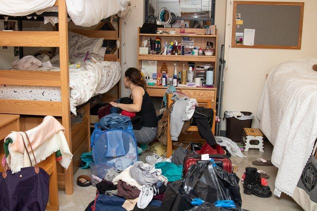 Студент перед ее двухъярусной кроватью в своей грязной комнате.