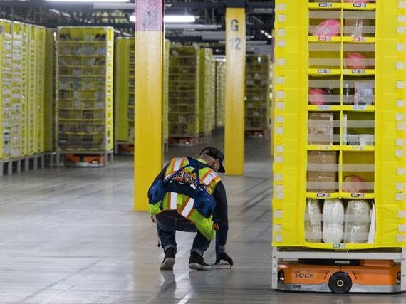 An Amazon worker retrieves a book that fell off a pod at the Amazon fulfillment center on Staten Island