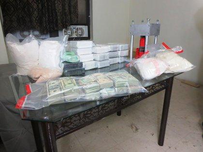 Money, meth, heroin and kilo press seized