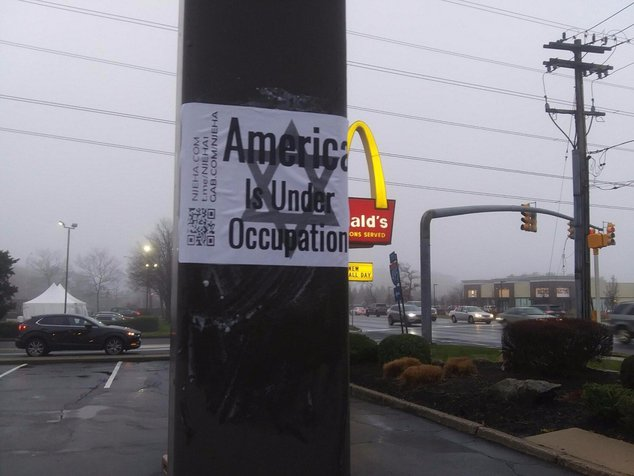 """A white supremacist sticker on a pole in New Jersey declares """"America is under occupation"""" over a Star of David."""