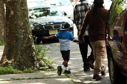 A child walks with an adult in East New York