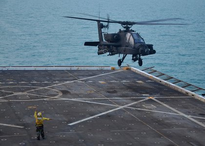 Aviation Boatswain's Mate (Handling) 3rd Class Hannah Marihugh launches an AH-64D Longbow Apache helicopter assigned to 3-159 Attack Reconnaissance Battalion off the flight deck of the amphibious transport dock ship USS New York