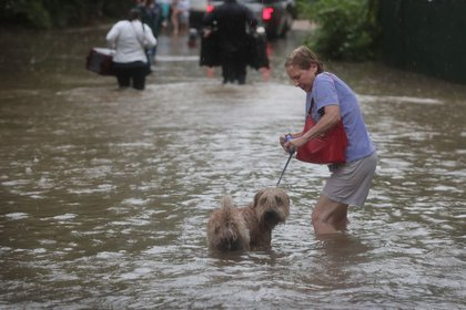 A resident walks down a flooded street in the upscale River Oaks neighborhood after it was inundated with water from Hurricane Harvey on August 27, 2017 in Houston, Texas<br>(Getty Images)