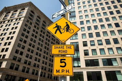 Signs alerting pedestrians, cyclists, and drivers to the new street rules near Broadway and West 24th Street.</br>