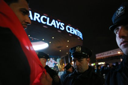 The protest was kettled for about 30 minutes by NYPD crowd control netting as Nets fans exited the arena.<br>