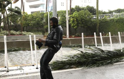 A man walks through the street as high winds and rain from Hurricane Irma arrive on September 10, 2017 in Miami, Florida.