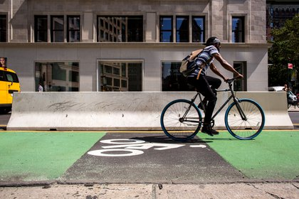 A cyclist uses a new protected bike lane to move east on West 25th Street.</br>