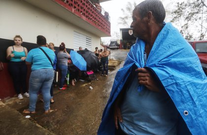 : Arian Rodriguez covers himself with a tarp as residents wait in the rain to register with FEMA more than two weeks after Hurricane Maria hit the island, on October 9, 2017 in Jayuya, Puerto Rico. <br/>
