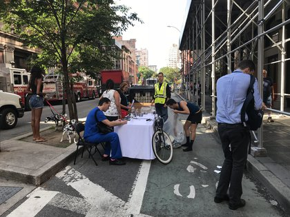 Dropping off contaminated belongings at 19th Street and Broadway. Dr. Neal Blitz sitting in blue, Steven Butschi with bike. (Jen Chung / Gothamist)