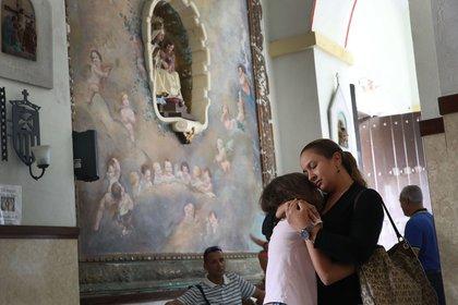 Orisnela Solano hugs her daughter, Laura Goenaga as they attend a church service at the Parroquia Nuestra Senora de la Asuncion church September 24, 2017 in Aibonito, Puerto Rico. (Joe Raedle/Getty Images)