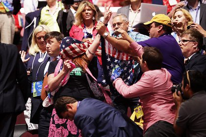 A protester is wrapped in an American flag by delegates. (Getty)