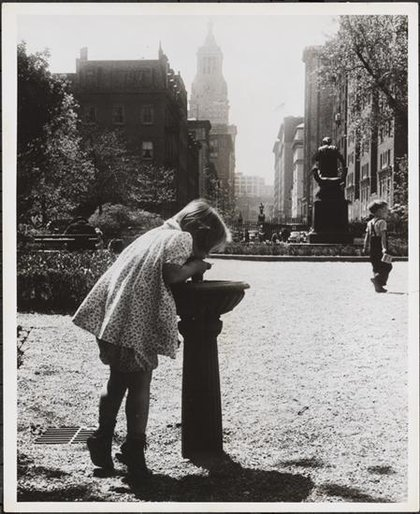 Office of War Information. 1944. View of a girl drinking out of a water fountain in Gramercy Park with the statue of Edwin Booth visible in the background. Visible beyond is the tower of the Consolidated Edison Co. Building at 4 Irving Place. (90.28.85)<br/>