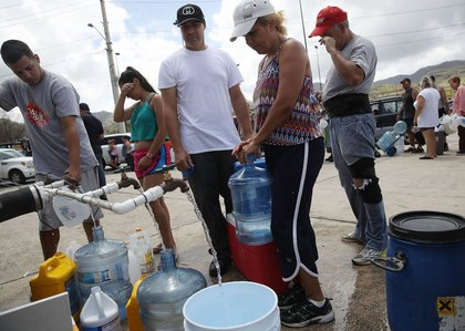 People wait in line for water as they wait for gas, electrical and water grids to be repaired on Sunday, September 24th in Aibonito, Puerto Rico. (Joe Raedle/Getty Images)