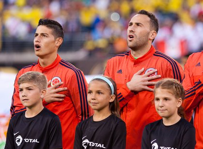 Colombia's James Rodriguez (left) and David Ospina sing their country's national anthem.