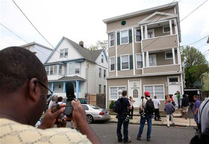 Neighbors gawk at the investigations at Shahzad's Bridgeport home