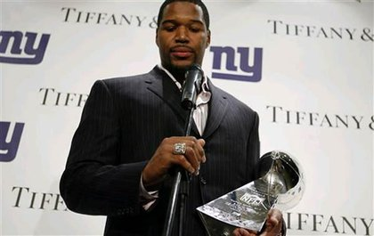 New York Giants defensive end Michael Strahan admires his Super Bowl ring while speaking to the press.