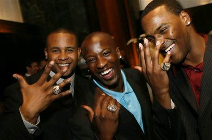 New York Giants running back Derrick Ward, left, cornerback Kevin Dockery, center, and cornerback Aaron Ross show off their rings.