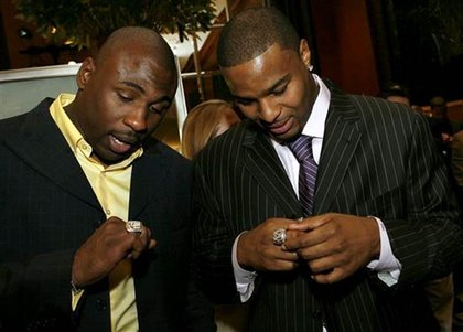 New York Giants running back Brandon Jacobs, left, and defensive end Osi Umenyiora admire their new Super Bowl rings.