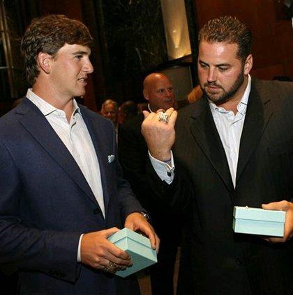 New York Giants quarterback Eli Manning, left, and center Shaun O'Hara admire their new Super Bowl rings.