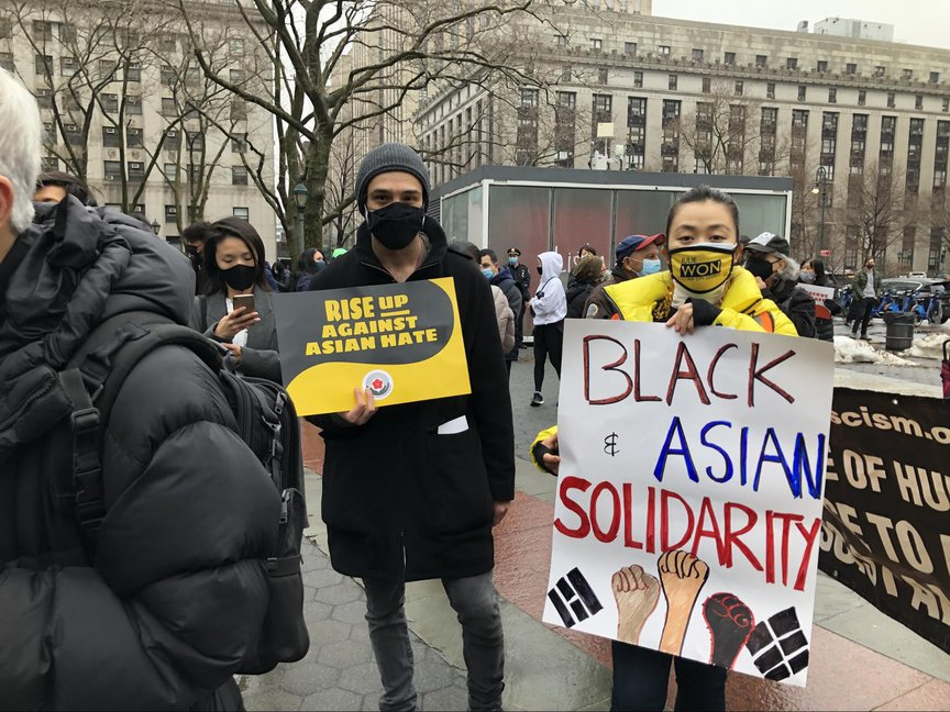 """People hold signs at the rally, including a sign that says """"Black and Asian Solidarity"""""""