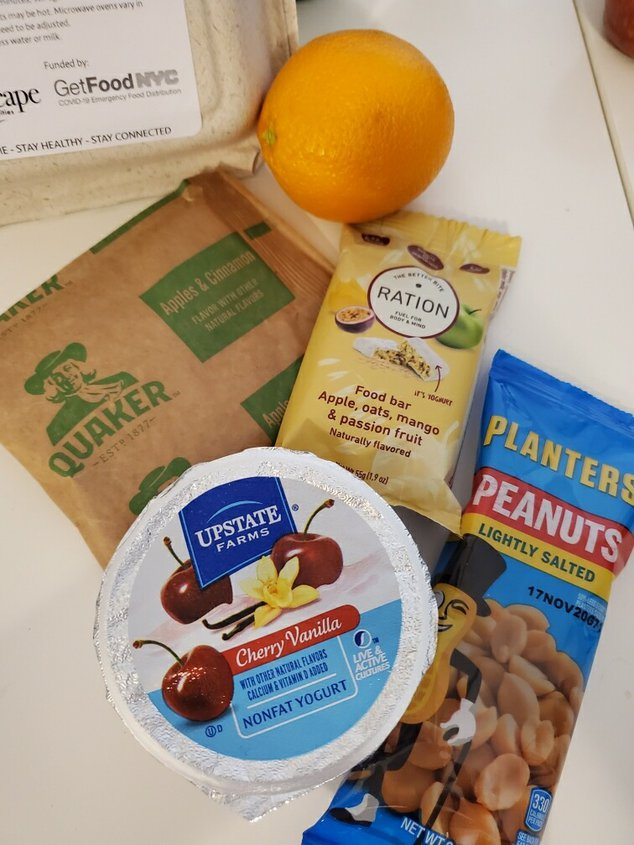 Snacks delievered as part of the GetFood NYC program including: peanuts, cherry yogurt, oatmeal, a granola bar and an orange.