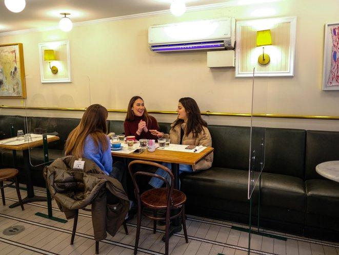 Three women sit inside, maskless, at a restaurant