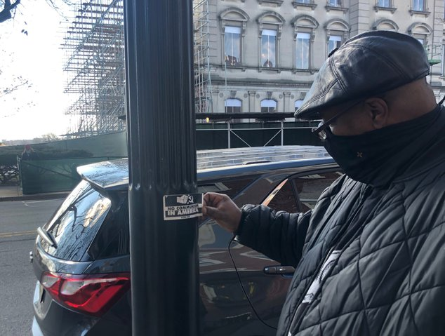 Daryle Lamont Jenkins removes a NJEHA sticker that he found across the street from the NJ statehouse.