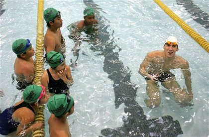 Phelps instructs young swimmers.