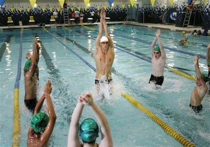 Michael Phelps showing some young swimmers some tricks.