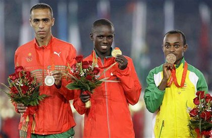 From left, silver medalist from Morocco Jaouad Gharib, Kenya's Samuel Kamau Wanjiru who won gold, and bronze medalist from Ethiopia, Tsegay Kebede, receive their medals for the men's marathon during the closing ceremonies.