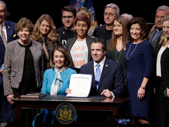 """Governor Andrew Cuomo, joined by House Speaker Nancy Pelosi, signs New York's """"red flag"""" gun control bill into law."""