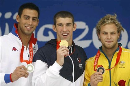 Phelps with his seventh gold medal, flanked by silver medalist Cavis and bronze medalist Andrew Lauterstein.