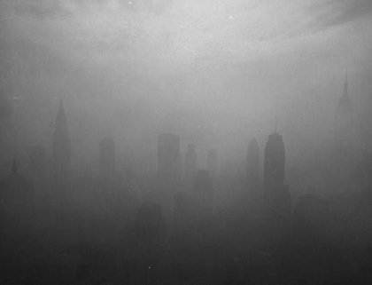 """November 12th, 1953. """"Midtown scene showing the Chrysler Building, Empire State & surrounding buildings enclosed in clouds of smog under the downtown skyline."""""""